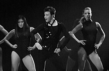 The grayscale picture of three people, two women and a man, who dance and put their hands on their hips. The man wears a dark outfit, compound of a vest, a shirt and pants, the women wear similar leotards.
