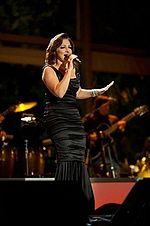 Une femme vêtue d'une robe noire se produit sur scène.
