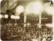 A photograph showing a large number of men seated on semi-circular tiers in a vaulted chamber as a large crowd looks on from an arcaded balcony