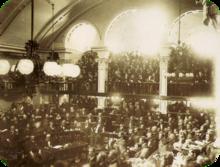 Uma fotografia que mostra um grande número de homens sentados em níveis semi-circulares em uma câmara abobadada como uma grande multidão olha sobre a partir de uma varanda com arcadas