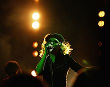 A woman wearing a black hat and shirt singing into a microphone.