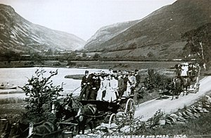 "Corris Railway - Horse-drawn charabancs owned by the Corris Railway pass Tal-y-llyn Lake on the ""Grand Tour"""