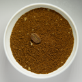 Grounded coffee beans in white bowl with intact roasted bean.png
