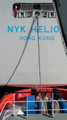 Hafenschlepper Boxter macht achtern an Containerschiff NYK HELIOS fest.png