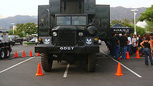 "A large, grey truck sits in a parking lot, surrounded by orange cones. People file into the truck via a queue on one side. The truck is branded with ""Halo"" and ""ODST"" markers."