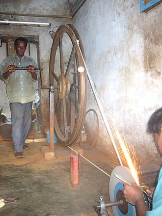 Sharpening - A two-man team sharpen a knife at high speed in Chennai, India