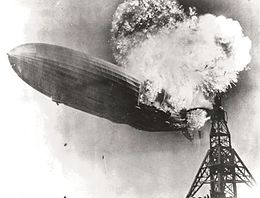 A large zeppelin, next to a skeletal tower,  burns violently in midair with a fireball larger than the zeppelin  itself rising from the zeppelin's rear third.