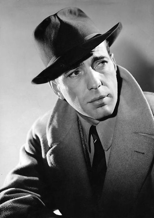 Black-and-white photo of Humphrey Bogart in 1940—a charming white man with dark eyes and a square face, wearing a dark hat and a light-colored overcoat, around 35 years of age.