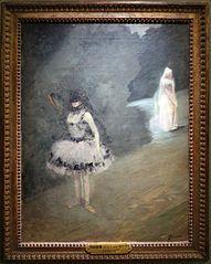 Danseuse debout derrière un portant de coulisse