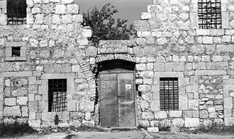 """Jerusalem Khan Theatre - Southwestern entrance before reconstruction. The sign reads: """"wood and refrigerators factory, also electric"""""""