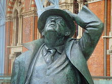 A bronze statue of an old man, wearing a suit and tie and an open long coat, looking up and holding a hat on his head with his left hand; behind, part of a brick building with Gothic arched windows