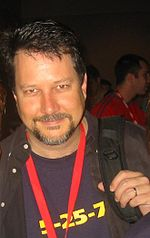 A man in his forties is seen wearing a backpack and a red necklace.