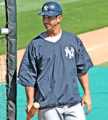 Jorge Posada stands next to the batting cage wearing a New York Yankees windbreaker