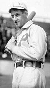 "A black-and-white photograph of a man in a white baseball uniform with the letter ""P"" over the left side of his chest holding a baseball bat over his right shoulder."