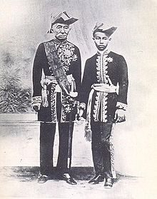 Black and white photo of older man and teenage boy standing in uniforms with bold designs and ornaments