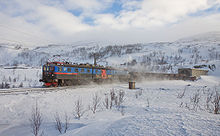 A three-unit locomotive hauls an ore train out of a tunnel, surrounded by snow.