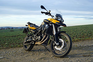 Black and yellow motorcycle parked on the edge of a field