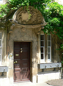 A large decorated shell-like stone canopy, with a shield in the centre and carved foliage around; beneath it, a wooden door with brass handle and knocker, set into a stone building; foliage grows above and around the canopy