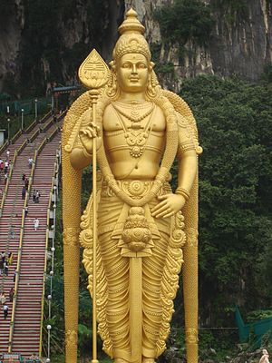 Hinduism in Malaysia - A Golden Lord Murugan Statue viewed from the ground before entering the Hindu Batu Cave temple.