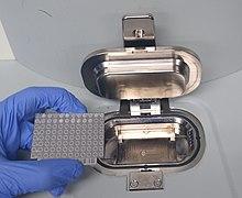 Eldivenli bir el, MALDI-TOF aletinin örnekleme alanına yüklemeye hazır, mikrobiyal örneklerin yerleştirildiği metal bir plakayı tutar.