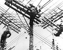 Three men climbing electric poles.