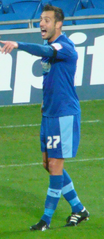 A man wearing blue shirt, shorts and socks, standing on a grass field