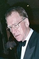 A long-faced man in a suit; he wears spectacles and his short-cropped hair is greying at the edges.