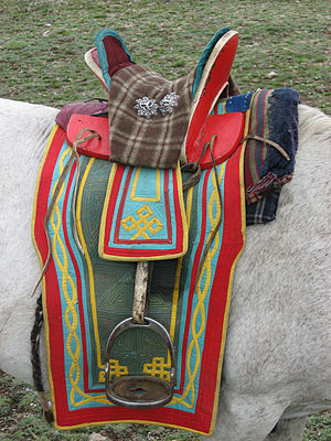 Horse culture in Mongolia - The Mongolian saddle, showing short stirrups, high pommel and cantle, and distinctive metal discs.