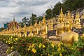 Multiple rows of golden statues of the Buddha seated with flowers, at Wat Phou Salao, Pakse, Laos.jpg