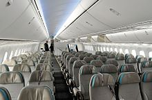 Airliner cabin with two aisles and rows of triple seats.
