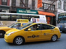 Two yellow taxis on a narrow street lined with shops.
