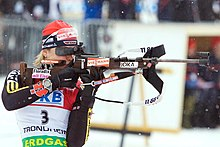 A woman in multicoloured winter sportswear, wearing a red cap and a jersey with the number 3, holds a rifle in a horizontal position. Her rifle has advertising on its side, while snow falls in the background.