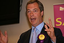 A photograph of a middle-aged white man with grey hair. His mouth is open and his arms are raised, near to his shoulders, suggesting that he is giving a public speech. He is wearing a black suit jacket with alight blue shirt and mauve tie. A purple and yellow UKIP rosette is attached to his jacket.