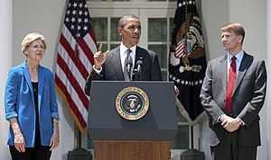 Elizabeth Warren - Warren stands next to President Barack Obama as he announces the nomination of Richard Cordray as the first director of the CFPB, July 2011.