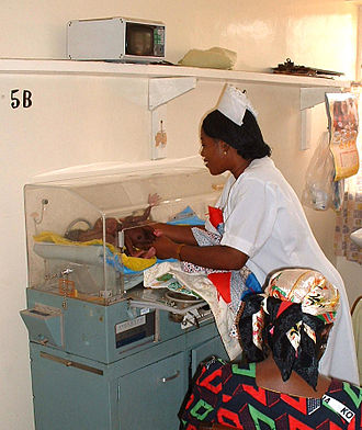 Neonatal intensive care unit - A pediatric nurse checking recently born triplets in an incubator at ECWA Evangel Hospital, Jos, Nigeria