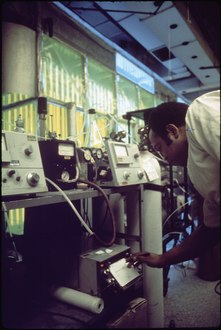 OLIN MOSS, INSTRUMENT TECHNICIAN ON AIR SANITATION CALIBRATING HYDROCARBON ANALYZERS. SMOG - NARA - 542765.tif