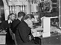 Officers at work in the decoding office of HMS SHEFFIELD during an Arctic convoy to Russia, December 1941. A6899.jpg
