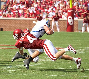 College football player tackling opposing player