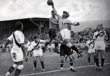 Photograph of a goalkeeper slapping a football out of his area