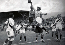 An action shot from a football match. A goalkeeper jumps and punches the ball away from his goalmouth