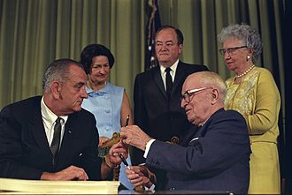 Bess Truman - President Johnson handing former President Truman a pen used to sign the  medicare bill as Bess, Lady Bird Johnson, and Vice President Humphrey look on.