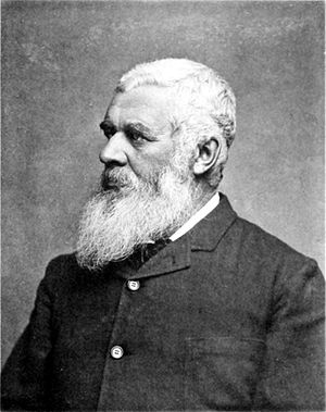 Black and white photograph of a man with a long white beard wearing a suit.