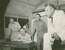 "In a ""war room"", three military men watch a worried man in civilian dress"