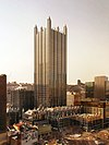 an all glass building with no other tall buildings around it. It is topped off by a glass spire on each corner and is surrounded by much shorter but similarly Gothic glass buildings.