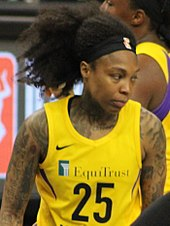 Waist high portrait of young woman with tattoos on her arms wearing yellow basketball uniform with lot of dark hair swept up into a high ponytail