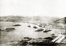 A black and white shot of several ships lying submerged underwater in various states of capsizing, a white building is shown in the right corner of the foreground.