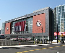 "A red and black building with large glass towers on either side is seen in the background.  The words ""Prudential Center"" are on top in white.  A parking lot and street are visible in the foreground."