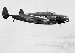 Twin-engined twin-tailed military monoplane in flight, side-on