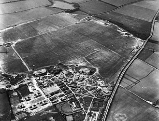 RAF Wittering - RAF Wittering after the attack on 14 March 1941. Bomb damage can be seen to the roof of the left-most hangar.  The runway linking RAF Wittering to Collyweston Landing Ground had not yet been constructed. WWII IWM HU 91901