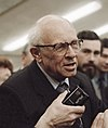 An elderly man with receding white hair and large spectacles, Andrei Sakharov, is being interviewed. A tape recorder is held in front of his mouth by a hand from the bottom of the photograph. Sakharov is wearing a suit with a blue and brown striped tie.